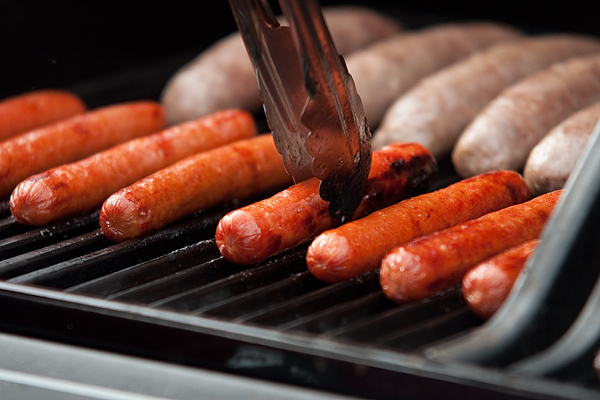 A grillmaster adjusts his hot dogs so that they all line up and cook evenly.