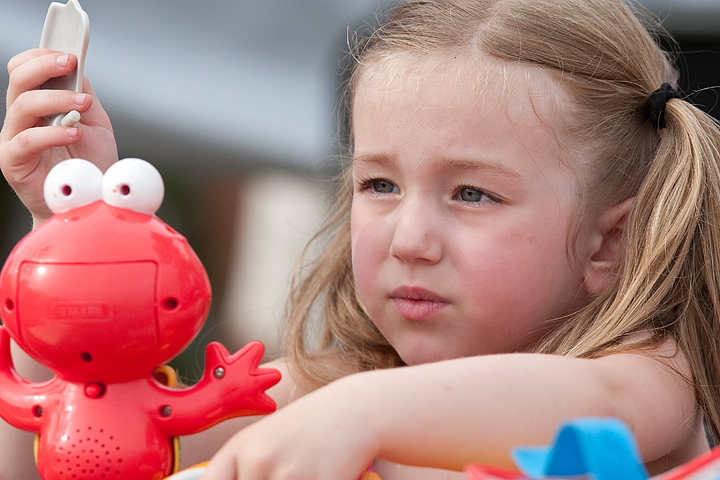 A young girl plays with an Elmo toy before a St. Paul Saints game on June 23, 2009.