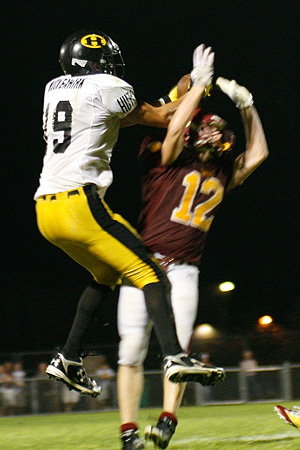 Hutchinson senior Brad Muckenhirn makes a leaping catch through the arms of Northfield's Ben Truax on during a 19-14 Hutchinson victory on Sept. 18, 2009 in Northfield, Minn.