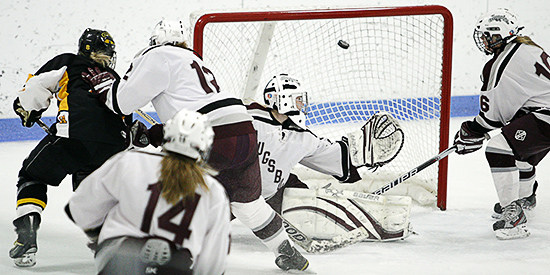 Augsburg goalie Brianna Schulz was powerless to stop No. 7 Gustavus's potent offense including this goal by Mollie Carroll (left) in the third period of a NCAA Div. III women's hockey between Augsburg vs. Gustavus Adolphus. Gustavus won the contest 9-0, including 4 goals scored by forward Allie Schwab (not shown). (Caleb Williams/d3photography.com)