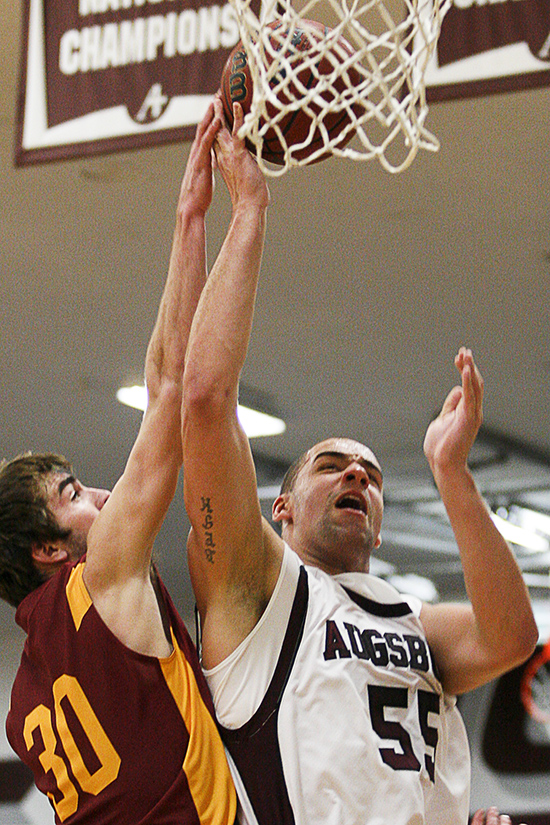 Augsburg center Cory Polta puts up a shot over Concordia-Moorhead's Aaron Lindahl during a game between the Auggies and the Cobbers on December 3, 2011 in Minneapolis. Polta had a career high 27 points in the contest, earning M.I.A.C Men's Basketball Player of the Week for his efforts. (Caleb Williams/d3photography.com)