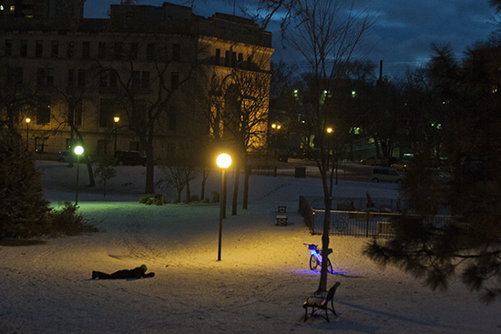 A man lays down in the snow to take a picture of his custom bicycle in Loring Park near downtown Minneapolis, Minn. on the evening of Jan. 1, 2012.