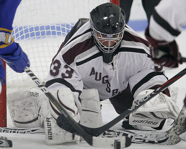 MINNEAPOLIS -- Augsburg goaltender Alex Hall reaches for the puck during a scramble in front of the net during the third period of a 1-1 draw with the College of St. Scholastica. Hall made 44 saves during the game, her third of the season.