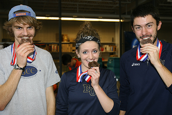 Bethel Cross Country runners Matt Berens, Mollie Gillberg and Zach Haskins bit their medals after competing in the 2012 NCAA Central Region Cross Country Championships at St. Olaf College in Northfield, Minnesota on November 10, 2012. Berens (7th), Gillberg (18th) and Haskins (4th) each earned a berth in the NCAA Division III Cross Country Championships on November 17 in Terre Haute, Ind.