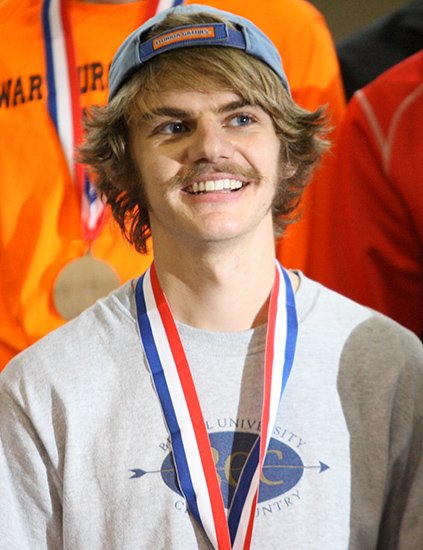 Matt Berens, illuminated by a photographers flash, poses on the award stand.