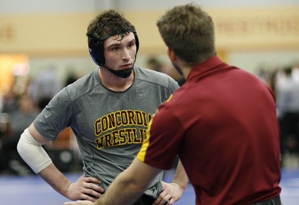 Concordia Moorhead 184 pound wrestler Chris Harrison listens to head coach Matt Nagel during pre match preparation for a match with Wartburg College at the NWCA national dual.