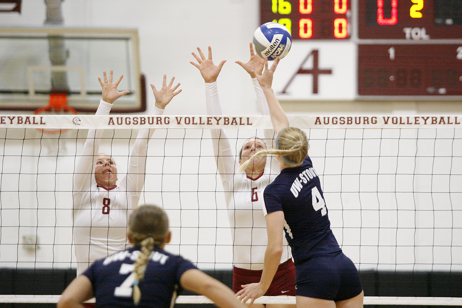 Augsburg volleyball players Jessica Lillquist (8) and Colleen Ourada (6) go up for a block in the first set of a match between UW-Stout on September 11, 2014. Augsburg won 3-2 (25-12, 15-25, 25-18, 18-25, 15-9).