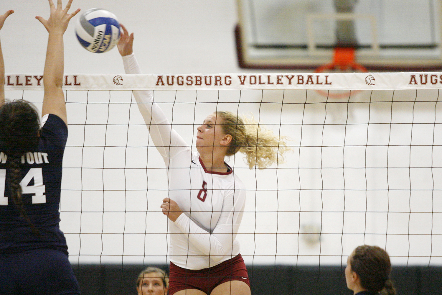 Augsburg volleyball player Jessica Lillquist (8) goes up for shot against UW-Stout's Ashley Pratt (14) n the first set of a match between UW-Stout on September 11, 2014. Augsburg won 3-2 (25-12, 15-25, 25-18, 18-25, 15-9).