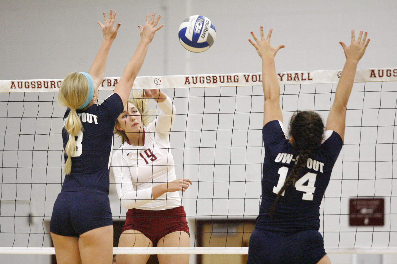 Augsburg volleyball player Ashley Peper (19) spikes against UW-Stout's Becky Bradshaw (8) and Ashley Pratt (14) in the first set of a match between UW-Stout on September 11, 2014. Augsburg won 3-2 (25-12, 15-25, 25-18, 18-25, 15-9). Peper had 14 kills.