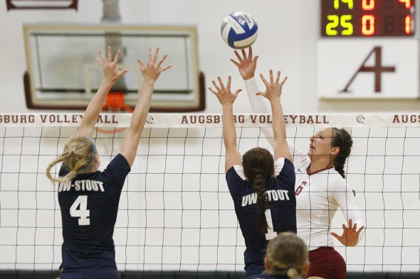 Augsburg volleyball player Colleen Ourada (6) tips the ball over UW-Stout's Morgan Denny (4) and Karley Wiensch (1) in the first set of a match between UW-Stout on September 11, 2014. Augsburg won 3-2 (25-12, 15-25, 25-18, 18-25, 15-9). Ourada had 14 kills.